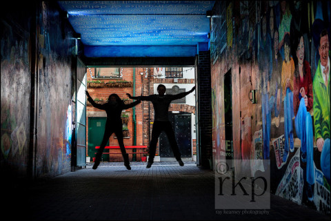 Couple leaping in alleyway in Belfast