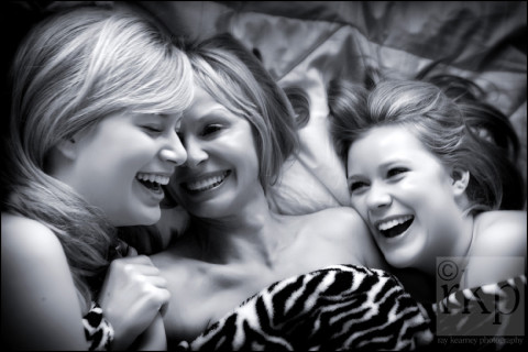 Mum and daughters laughing in bed