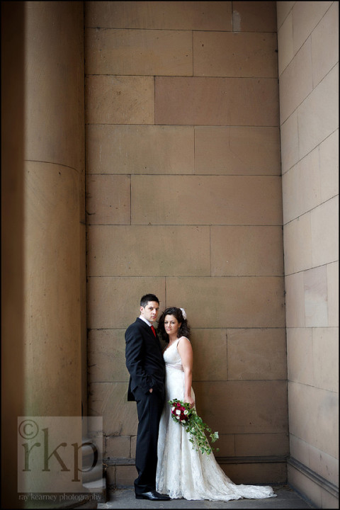 Bride and Groom standing by the pillars at the Old Courthouse, Knutsford
