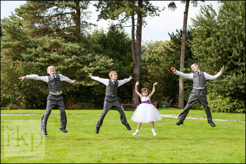 Flower girl and page boys doing star jumps at Bartle Hall