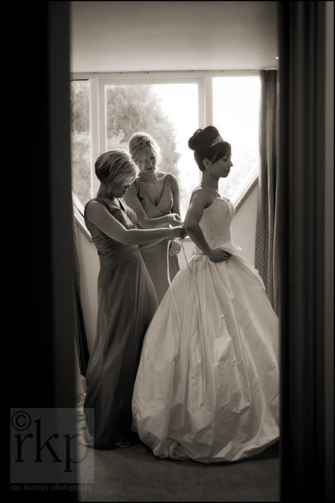 Bridesmaids lacing the Bride's dress at Thornton Manor